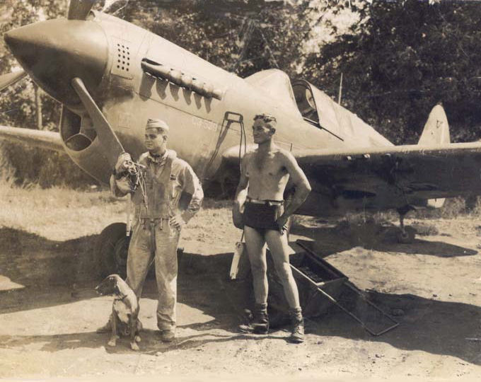 "Des Alexander and Dutch pilot with his P-40 Kittyhawk and pet dog ""Woden"" in Merauke"